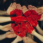 Hands all together, painted red to make a heart